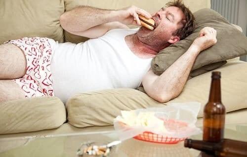 Мужчина пьет, курит, ест гамбургер