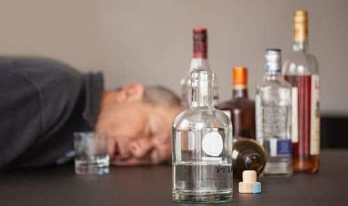 Пьяный спит в окружении бутылок