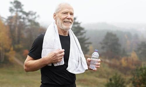 Пожилой человек на пробежке с бутылкой воды