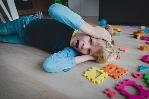 Ребенок кричит на полу возле игрушек