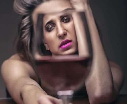 Женщина криво отражается в бокале