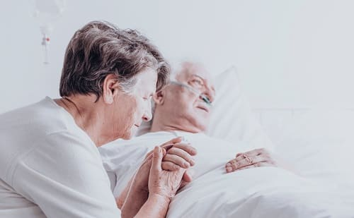 Женщина обнимает больного с тяжелой стадией Альцгеймера