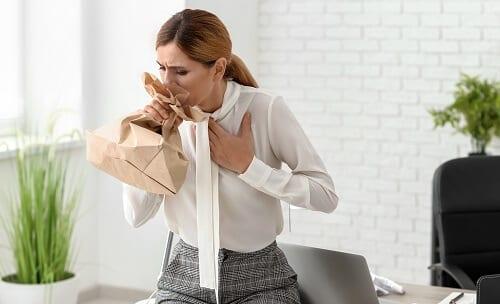 Женщина в стрессе дышит в пакет