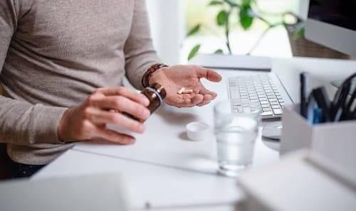 Принимаем таблетки у рабочего стола с компьютером