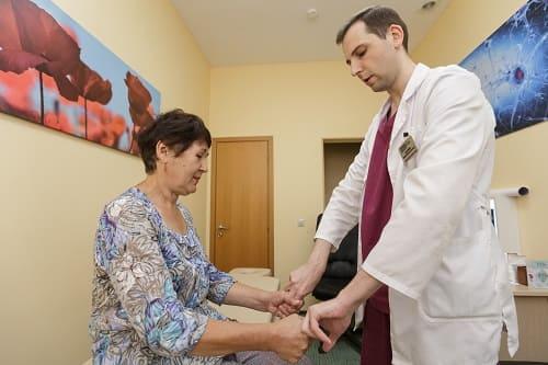 Невролог осматривает женщину с онемением рук