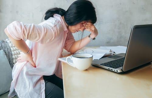 Усталая женщина в приступом остеохондроза и ВСД