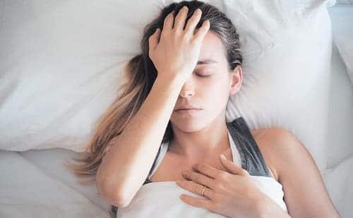 Женщина с головной болью утром в постели