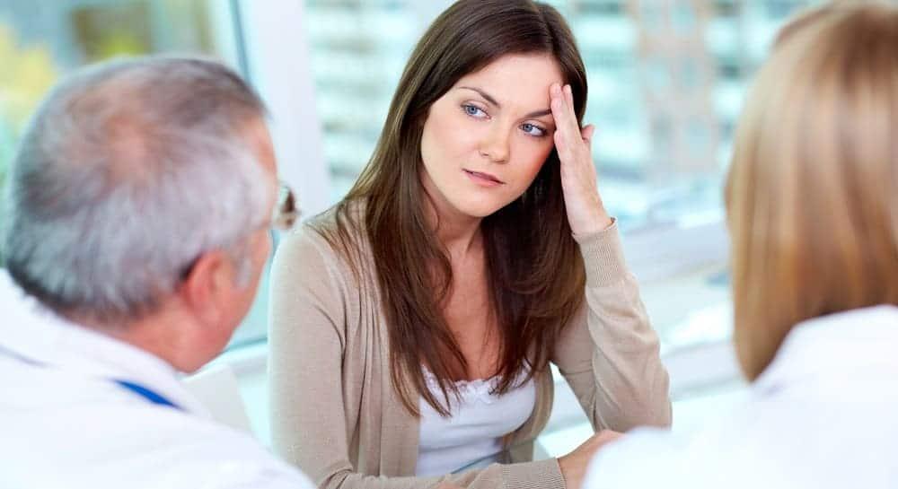 Женщина жалуется врачам на головную боль