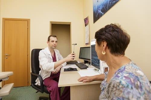 Невролог осматривает пациентку с лобно-височной болью