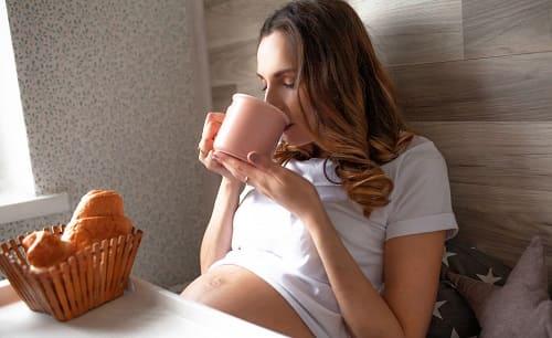 Беременная пьет чай с булочками
